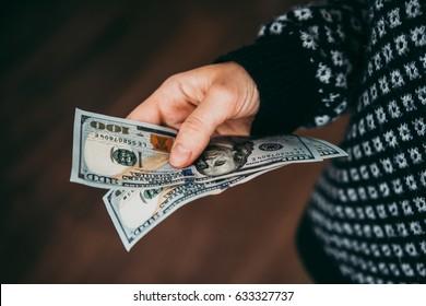 Hand holding us dollar bills