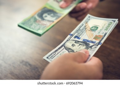 Hand holding US dollar bills trading with Australian dollars - money conversion and exchanging concept