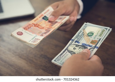 Hand holding US dollar bills trading with Russian ruble currency - money conversion and exchanging concept