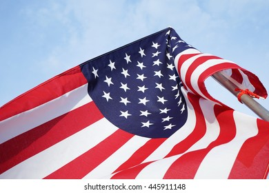hand holding USA flag on sky background