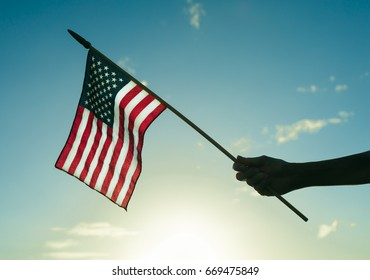 Hand holding up USA United States of America flag against a blue sky background.