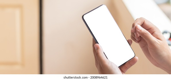 Hand holding and using smartphone with white blank on screen.