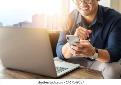 Hand, die per SMS telefoniert und Computer tippt.Geschäftsmann am Arbeitsplatz Denken Investitionsplan.chatting Kontakt Investor.Suchen Sie nach Informationen über Internet.Verbinden Menschen Konzept