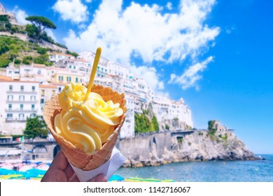 Hand is holding the vanilla ice cream. In the background is blue sky and coast. This is situated in the city Amalfi in Europe.
