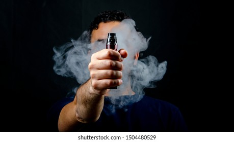 hand holding vape e-cigarette or electronic cigarette with white smoke over a black background.