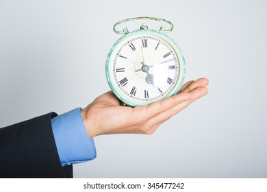 Hand holding vintage alarm clock. advertising or business concept, isolated on a gray background.