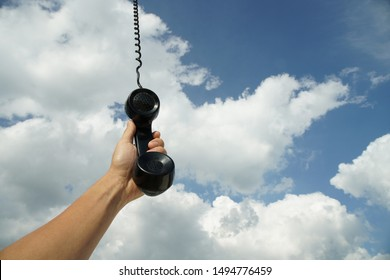 Hand holding vintage black phone with line hanging from the sky. Conceptual photography talking to someone from above