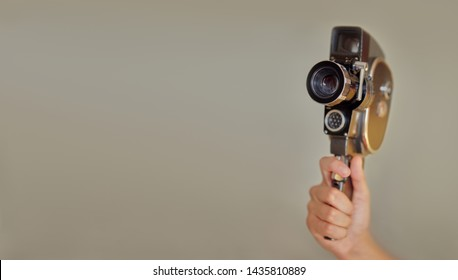 Hand holding vintage old movie camera with copy space on beige background