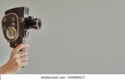 Hand holding vintage old movie camera with copy space isolated on beige background