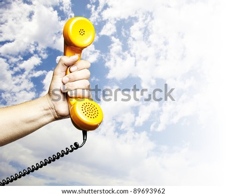 hand holding a vintage telephone against a blue sky background