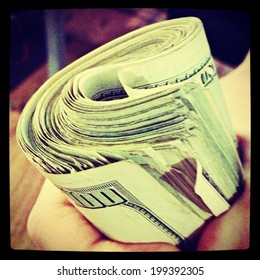 A hand holding a wad of cash with Instagram filter.