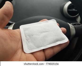 hand holding hand warmer in car