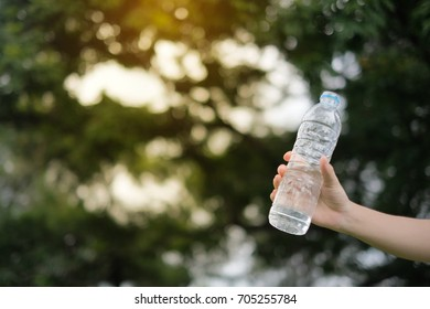 Hand holding water bottle in the park morning sunrise, Young woman drinking water after run, sport and healthy care concepts.