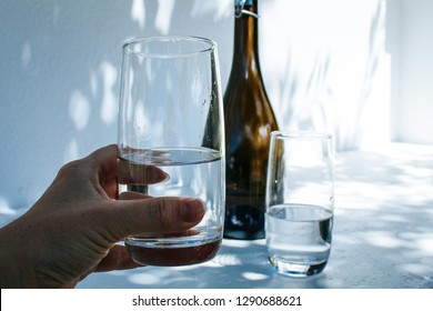 Hand holding a water glass in front of a bottle and another glass, isolated on a white concrete wall with shadows of leaves on it