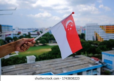 Hand holding waving Singapore flag outside HDB flat window. Due to coronavirus covid-19 outbreak, the 2020 National Day Parade would be broadcast remotely, people'd be celebrating from their homes.
