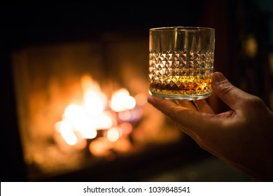 Hand holding whiskey glass at fireplace