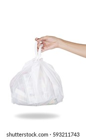 Hand holding white bag of rubbish on white background
