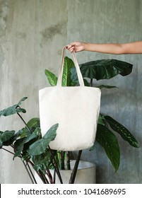 hand holding white blank linen nature canvas tote bag for mock up design. On tropical background