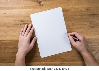Hand holding white blank paper sheet mockup on wooden background. Arm in shirt hold clear brochure template mock up. Leaflet document surface design. Simple pure print display show.