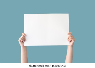 hand holding white blank paper isolated on blue background with clipping path