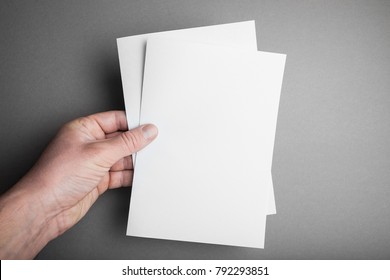 Hand holding white blank paper A5 sheet mockup. Leaflet document surface design.