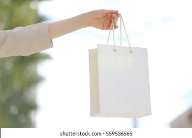 hand holding a white blank shopping bag