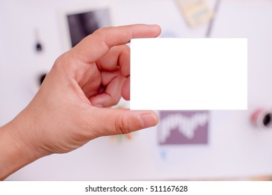 Hand is holding a white business card or white label On the desk in office.