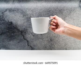 Hand holding a white ceramic mug