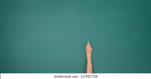 Hand holding white chalk and writing on green board.