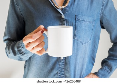 Hand holding a white coffee cup on denim shirt background. Mock up, perfect for putting your design on.