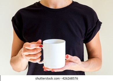 Hand holding a white coffee cup black t-shirt background. Mock up, perfect for putting your design on.