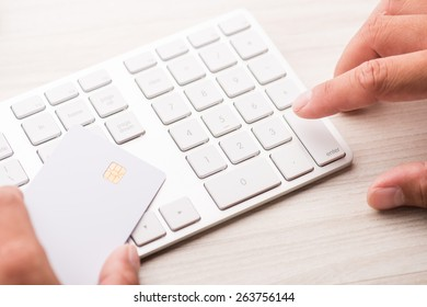 hand holding a white credit card and typing. On-line shopping on the internet