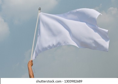 Hand up holding white flag pole the concept of give up.