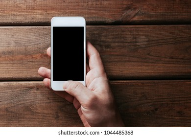 Hand holding white mobile phone with empty copy space black screen over brown wooden table.