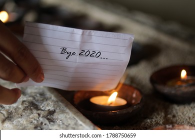 Hand holding a white note paper written - Bye 2020. Burning it on a burning candle in a ceramic bowl. Hope, new life and new year 2021 concept.