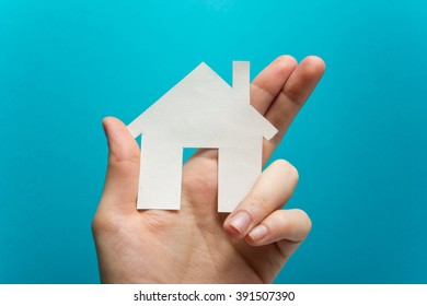 Hand holding white paper house figure on blue background. Real Estate Concept. Ecological building. Copy space top view.