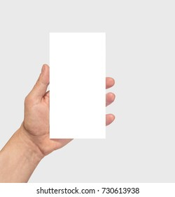 Hand holding white paper (sheet, board) phone size with copy space. Phone imitation.