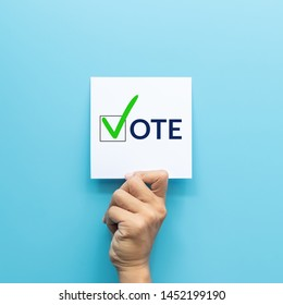 """hand holding white paper with the """"vote"""" and green check mark voting symbols in checkbox of the inscription isolated on blue background"""
