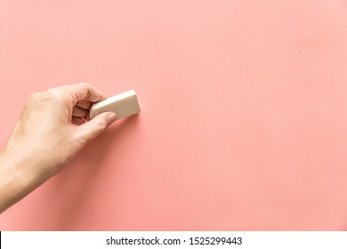Hand holding white rubber for erasing something on empty pink background. Abstract background with copy space.