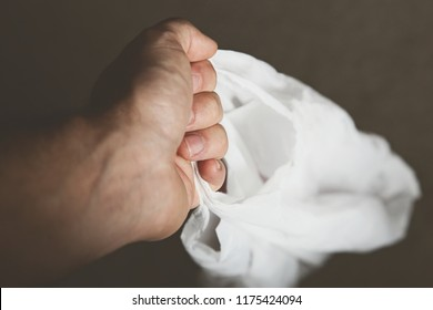 A hand holding a white single use plastic shopping bag.