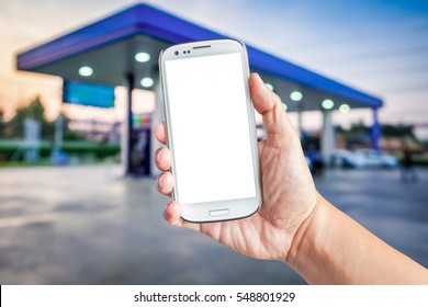 Hand holding a white smartphone with mockup blank screen blur background of twilight gas station at sunset. Touch screen mobile phone at the petrol station.