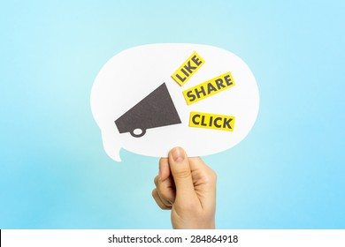 """Hand holding white speech bubble with megaphone and the words """"LIKE"""" """"SHARE"""" """"CLICK"""", on blue background. Social media and internet concept."""