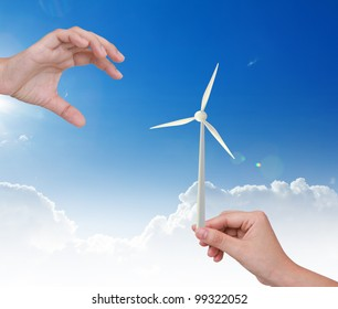 Hand holding Wind Turbine  over blue sky