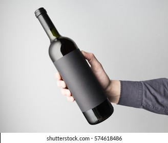 Hand is holding wine bottle