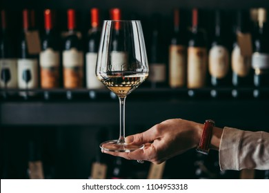 Hand holding a wine glass.