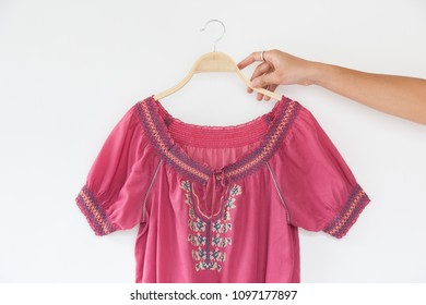 hand is holding Woman blouse with Pink blouse cotton on white background.