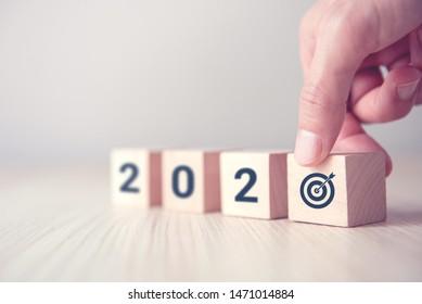 Hand, die Holzwürfel hält mit Neujahr 2020 und Tor Icon Konzept.
