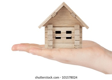 Hand holding wooden block house on a white background