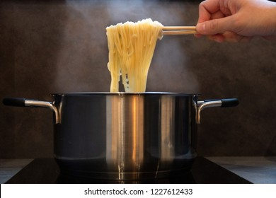 Hand holding wooden chopsticks of instant noodles or Ramen with smoke.Steam from hot soup bowl selective focus.Instant noodles is a convenient,delicious and cheap food.