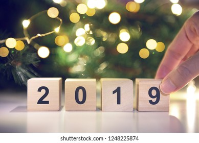 Hand holding Wooden cubes with Happy new year 2019 with light bokeh background.
